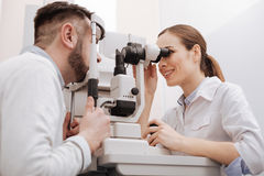 Joyful professional ophthalmologist scanning the eye of her patient Royalty Free Stock Photos