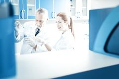 Joyful professional scientists conducting an experiment. Scientific discoveries. Joyful nice professional scientists standing together and looking at the test stock images