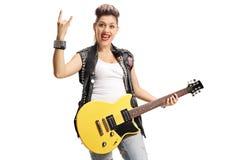Joyful punk girl with an electric guitar making rock hand gestur Stock Image