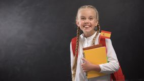 Joyful pupil holding books with tiny Spain flag, ready to learn foreign language. Stock footage stock footage