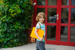 The joyful pupil on a schoolyard. Boy has fair curly hair and a nice face. Behind shoulders at the pupil a satchel, in hands the folder. The schoolboy with a Royalty Free Stock Photos