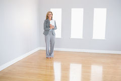 Joyful realtor standing in a room holding documents Stock Images