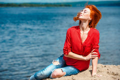 Joyful redhead woman flicking her hair in the air. Feeling serene and free and enjoying a sunny day at the beach Stock Photos