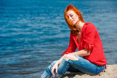 Joyful redhead woman sitting comfortably and smiling. Looks serene and free and enjoying a sunny day at the beach Royalty Free Stock Photos