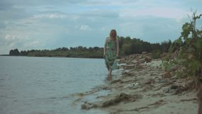 Joyful redhead woman walking along the beach. Joyful redhead woman in summer dress walking along a beach in shallow water at the edge of the sea over beautiful stock video footage