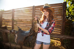 Joyful redhead young cowgirl preparing saddle for riding horse. At ranch Royalty Free Stock Images