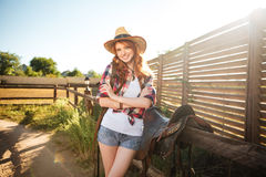 Joyful redhead young cowgirl preparing saddle for riding horse. At ranch Royalty Free Stock Image