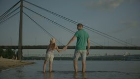Happy family enjoying weekend on riverbank stock footage