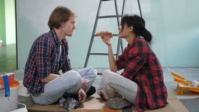 Cute diy couple sharing pizza during home makeover