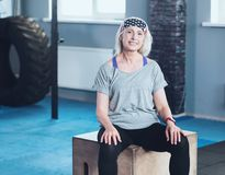 Joyful retired lady resting on wooden box in fitness club. Active retirement. Happy senior woman in a sportswear smiling into the camera while having a rest Stock Photography
