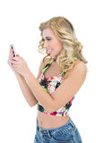 Joyful retro blonde model looking at her mobile phone Royalty Free Stock Images