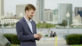 Joyful rich man is counting his money on a street stock footage
