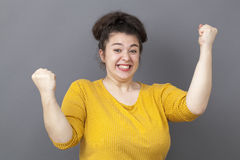 Joyful 20s big woman expressing fun victory Stock Images