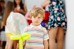 Joyful or sad kid boy on birthday party with an air balloon Royalty Free Stock Photography
