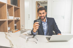 Joyful salesman proposing design object Stock Image