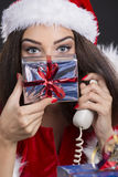 Joyful Santa girl with gift box. Joyful Santa girl speaking on phone and hiding her face with a gift box over dark background Stock Images