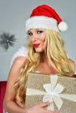Joyful Santa woman holding present posing pretty in Christmas decorated studio. Royalty Free Stock Photo