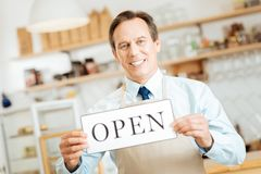 Joyful satisfied man looking straight and showing the plate. Real entrepreneur. Joyful confident satisfied man standing in the cafe looking straight and showing Royalty Free Stock Photos
