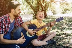 Joyful and satisfied young boy is holding guitar and playing on it. He is singing and keeping eyes closed. His father is royalty free stock photos