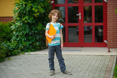 The joyful schoolboy on a schoolyard. Chappy has curly hair and a nice face. Behind shoulders at the pupil a satchel, in hands the folder. The schoolboy with a Royalty Free Stock Photo
