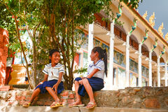 Joyful Schoolgirls Giggling Outside Temple on Tonle Sap Lake, Cambodia. Two young girls sitting on steps in their school uniforms during a classroom break Stock Image