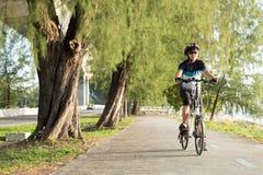 Senior Asian woman riding a bicycle. Joyful senior Asian woman riding a bicycle in park stock image