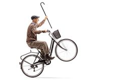 Joyful senior with a cane riding a bicycle and doing a wheelie. Isolated on white background Royalty Free Stock Image