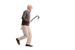 Joyful senior carrying a cane and running Stock Image