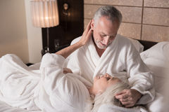 Joyful senior couple having fun on the bed stock photography