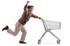 Joyful senior with 3D glasses running and pushing an empty shopping cart royalty free stock photo