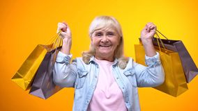 Joyful senior female holding shopping bags, pleasant leisure time, advertisement royalty free stock photography