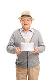 Joyful senior gentleman holding a birthday cake. Vertical shot of a joyful senior gentleman holding a birthday cake and smiling isolated on white background Royalty Free Stock Images