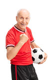 Joyful senior with gripped fist holding a football Royalty Free Stock Photography