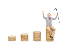 Joyful senior holding cane seated on pile of coins Royalty Free Stock Image