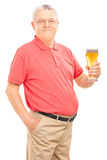 Joyful senior holding a pint of beer. Isolated on white background royalty free stock image