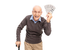 Joyful senior holding a stack of money. Studio shot of a joyful senior holding a stack of money and looking at the camera isolated on white background royalty free stock photography