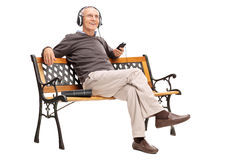 Joyful senior listening to music from on cell phone Royalty Free Stock Photos