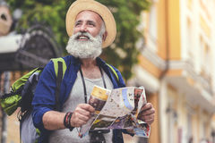 Joyful senior male traveler enjoying walk in town. Portrait of excited old man traveling in city. He is holding map and looking around with interest. Tourist and Stock Photo