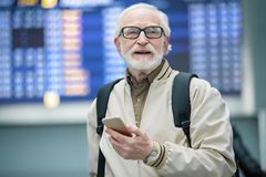 Joyful senior male is waiting for his aircraft. Full of positive emotions. Portrait of cheerful bearded gray-haired man is standing at airport and holding mobile Royalty Free Stock Images