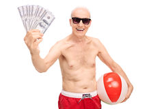 Joyful senior man holding money and a beach ball Stock Photography
