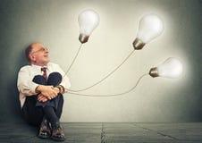 Joyful senior man holding three light bulbs having many idea Stock Photo
