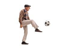 Joyful senior man kicking a football stock images