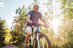 Joyful senior man riding a bike in a park on a beautiful sunny day. Active life in senior age. Concept of sport on vacation royalty free stock photos