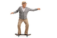 Joyful senior man riding a skateboard. Isolated on white background royalty free stock photo