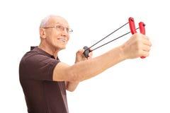 Joyful senior man shooting a slingshot Stock Photos