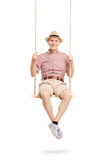 Joyful senior man sitting on a swing and posing. Joyful senior man in a checkered shirt sitting on a swing and posing isolated on white background Stock Images