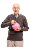 Joyful senior putting coin into a piggybank Stock Images