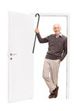 Joyful senior showing his cane and leaning a door Stock Photos