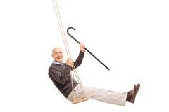 Joyful senior swinging on a swing Stock Photos