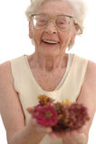 Joyful Senior Woman. Mature woman in her eighties smiling cupping flowers with her hands. Photographed on white royalty free stock image